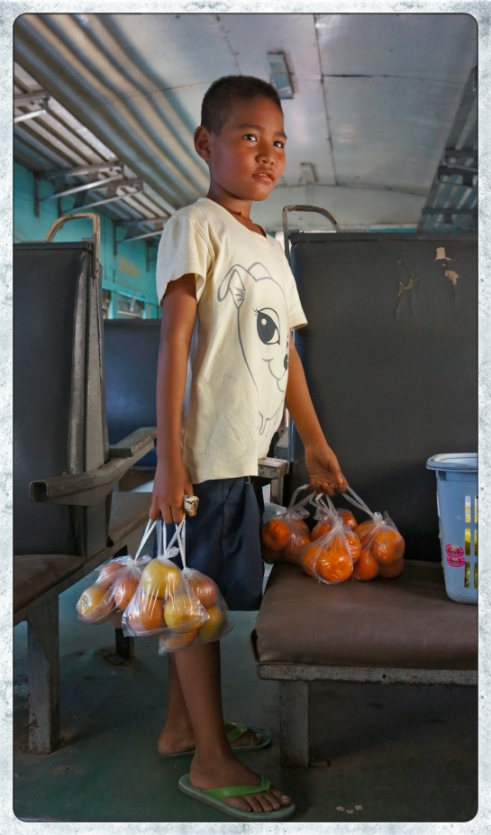 Boy selling apples and oranges